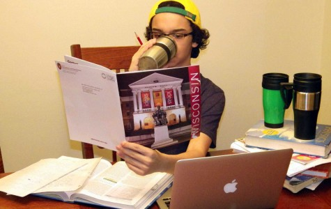 Ricardo Matias ('15) peruses a UW-Madison pamphlet while working on his Common Application and various homework assignments from school. If the three coffee mugs are any indication, it is going to be a long night for him.