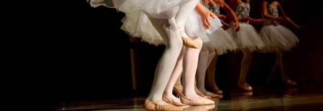 Ballerinas gracefully line up on stage in position to dance into the next move.