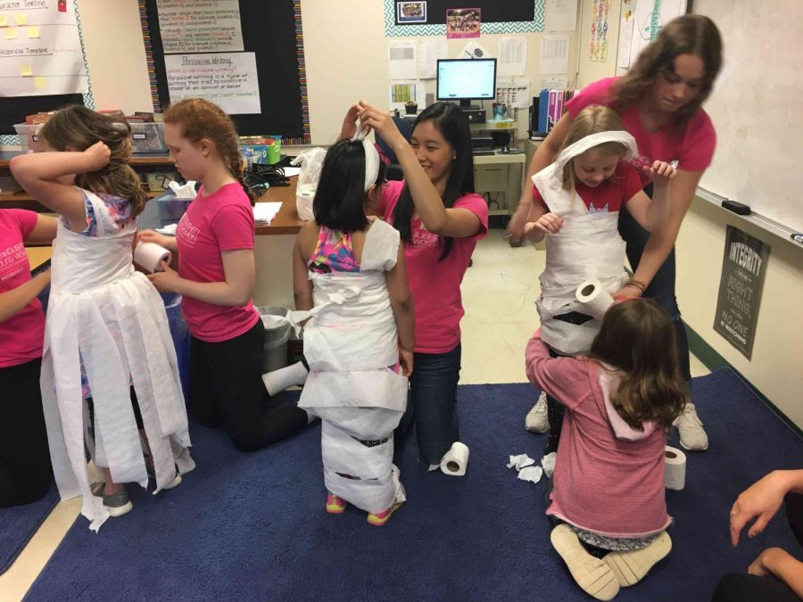 On High Interest Day, Tirzah Sonderman ('20), Harriet Huang ('18) and Caroline Tollar ('20) help little girls from Swanson Elementary design and wear toilet paper dresses to symbolize self expression, which is an important part of DYW.