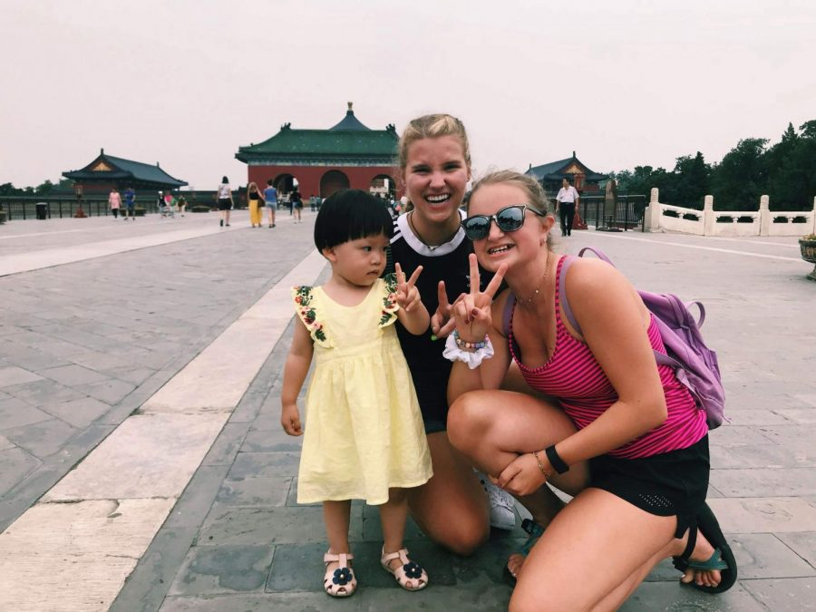 Hannah Thomas ('20) and Maggie Conlon ('20) teach a little girl how to pose with the two finger peace sign. Qiu Qiu, the little girl pictured, posed with other BC students as well. Interactions with people in China was a plus during the trip.
