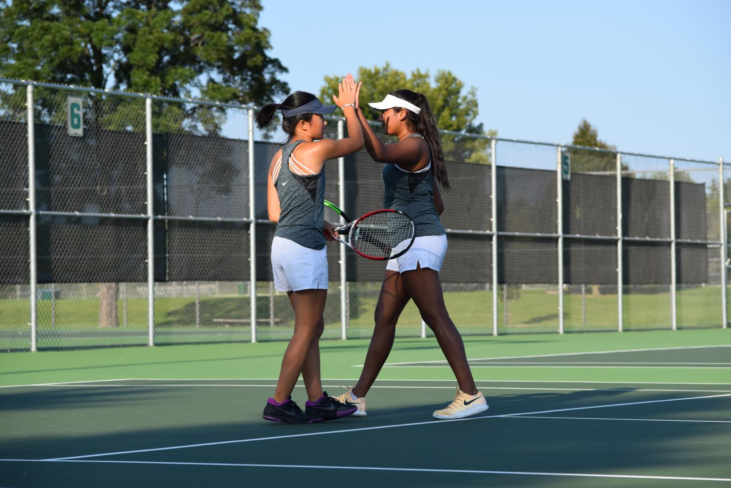 Varsity players Katherine Liu ('19) and Aafreen Sajid ('19) exchange high fives after a victorious doubles match on August 30.