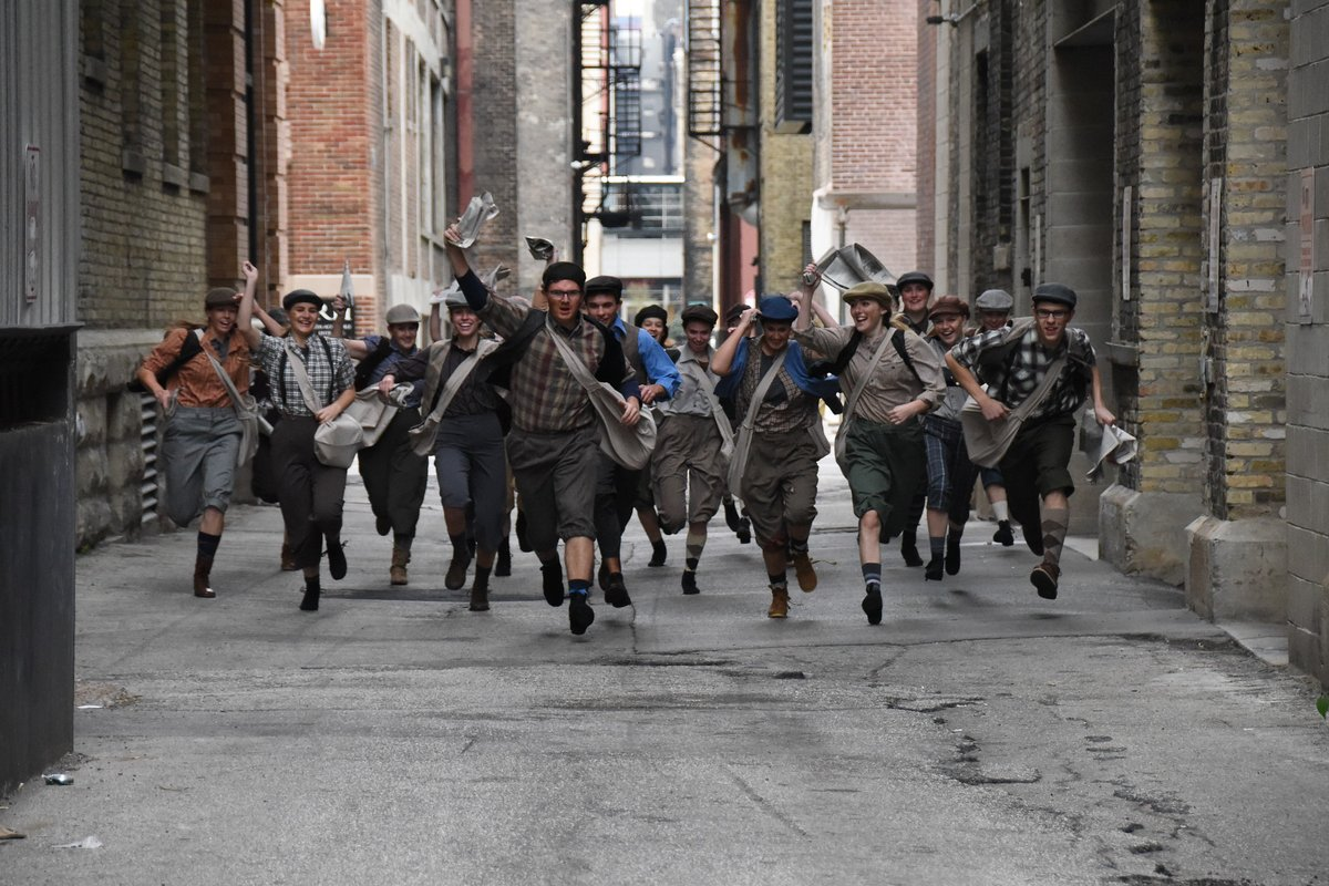 The Newsies cast runs towards the camera while taking cast photos. The cast performed at the Holiday Kickoff with the marching band and choir.