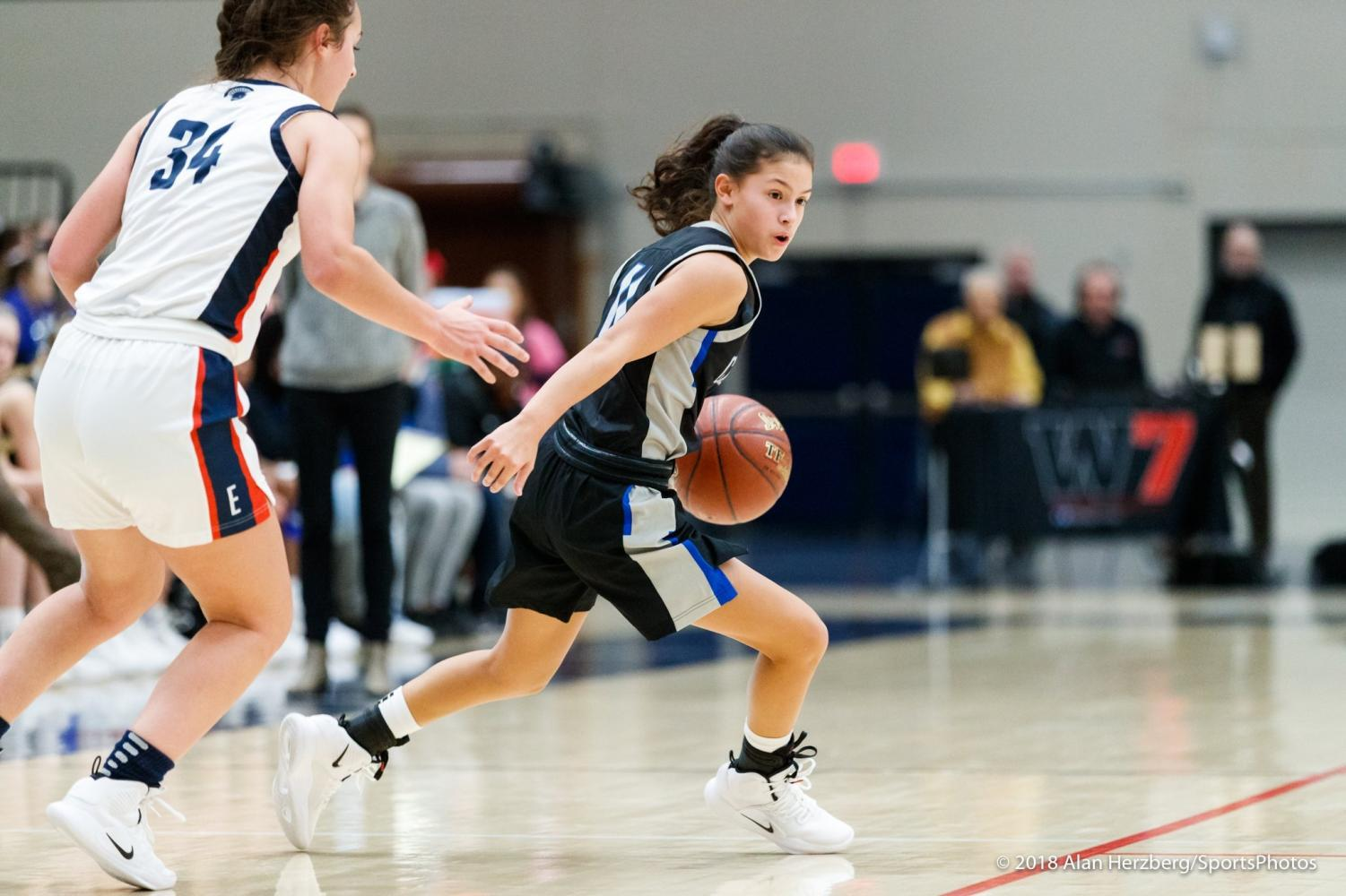 Varsity player CJ Romero ('21) drives the ball to the basket with intense concentration, an opposing player on her tail.