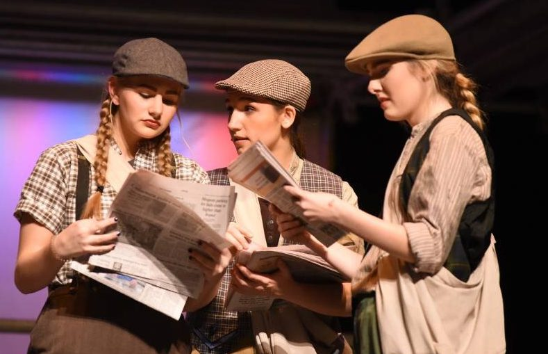 Makenna Lemke ('19), Eren Wolf ('19) and Hannah Hawthorne ('19) all look over a newspaper headline to determine what the best way to sell the 'pape' is