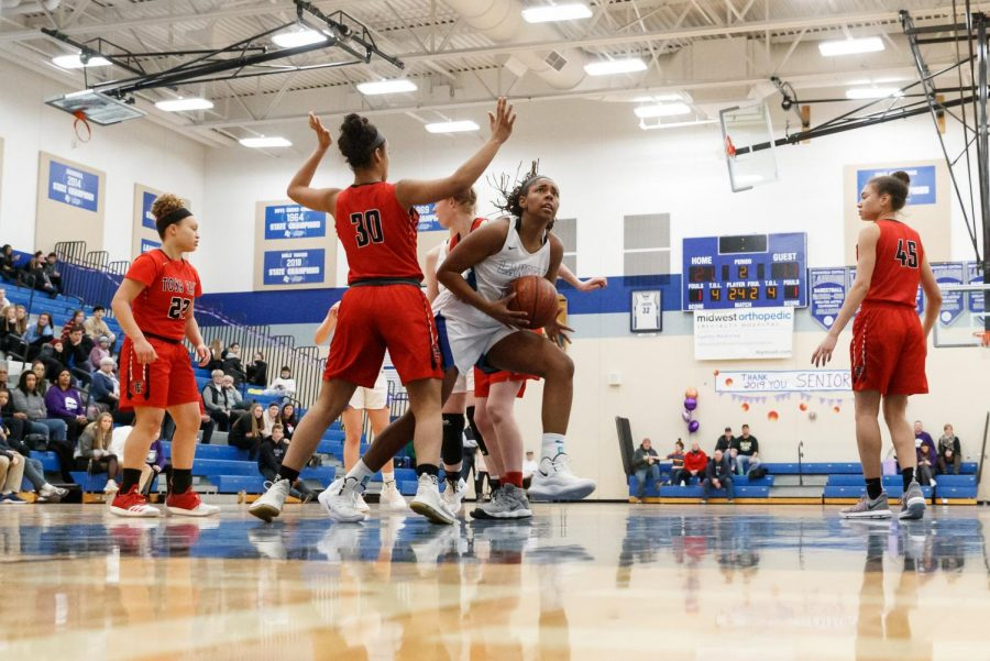 Elise Joplin ('19) looks to the basket amid a sea of red defenders from Tosa East. The girls basketball team won the game 47-30 to achieve a 16-9 record.
