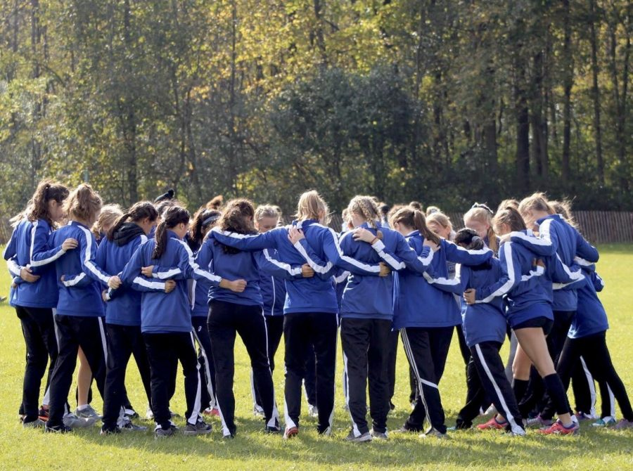 The+BC+Girls+Cross+Country+team+huddles+together+before+the+Eagle+Invite+at+UW+Parkside.+Junior+Varsity+finished+in+second+place+-+just+one+point+away+from+the+first+place+team.