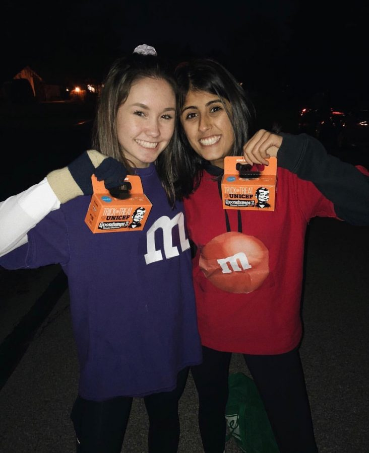 Riley Feng ('210) and Nisha Desai ('21) smile with their filled donation boxes after last year's Trick-or-Treat for UNICEF.