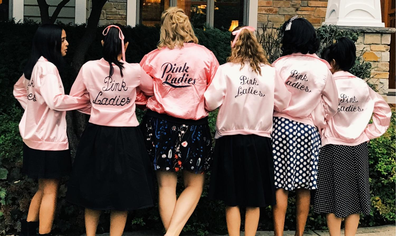 Junior girls don the iconic Pink Ladies jackets. Left to right: Lana Gharia, Vera Fong, Maggie LaRos, Allie Gosenheimer, Miriam Budithi, and Fuka Sunagawa