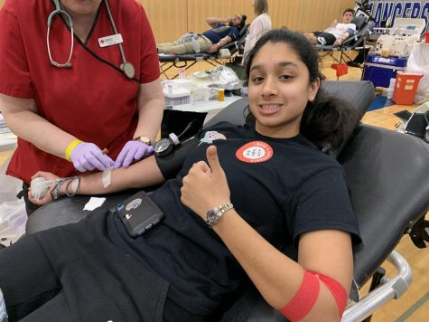 "Trisha Nandakumar ('21) gives a thumbs up while her blood is drawn. She reportedly fainted later on in her third block class. ""I felt fine for a while and just forgot to drink water.  Then, I started feeling really thirsty during class and that's when it happened. After fainting, I just drank water and went back to class, and I felt fine. I didn't realize that people were freaked out about it until I talked to my friends later,"" she said."