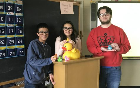 Liem Rao ('23), Alana O'Neill ('23), and Kaya Shaw ('22) smile with some ducks both off and new, with James Pond front and center on the podium. These three French 2 students, along with Megan Manganaro ('23), Khalil Towns ('23), and Alex Enaci ('23), helped bring in the newest batch of rubber ducks.
